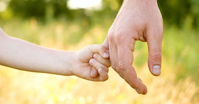 child holding fathers hand